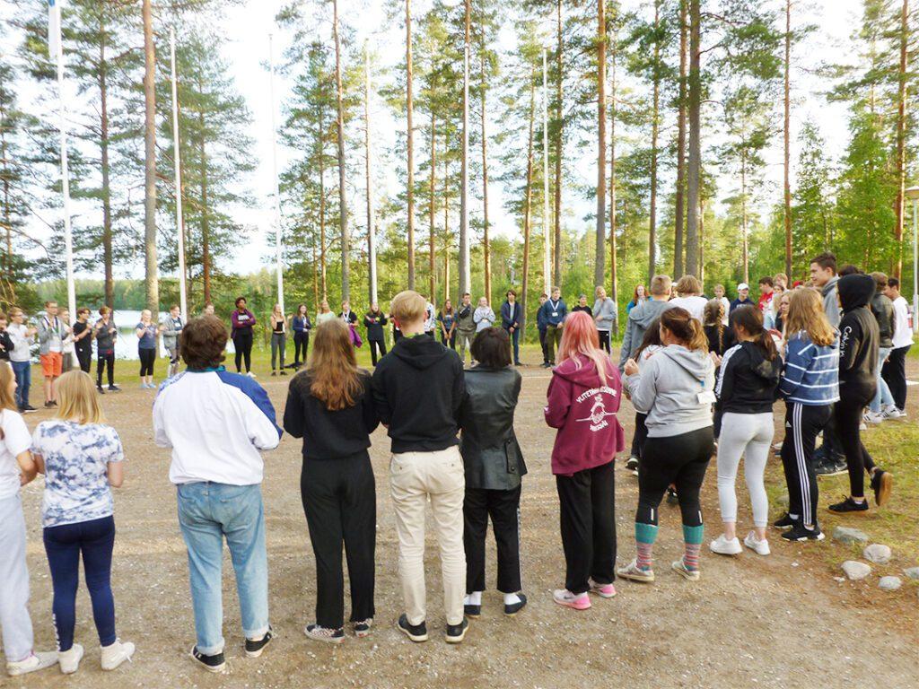 Nuoret seisomassa piirissä luonnon keskellä.