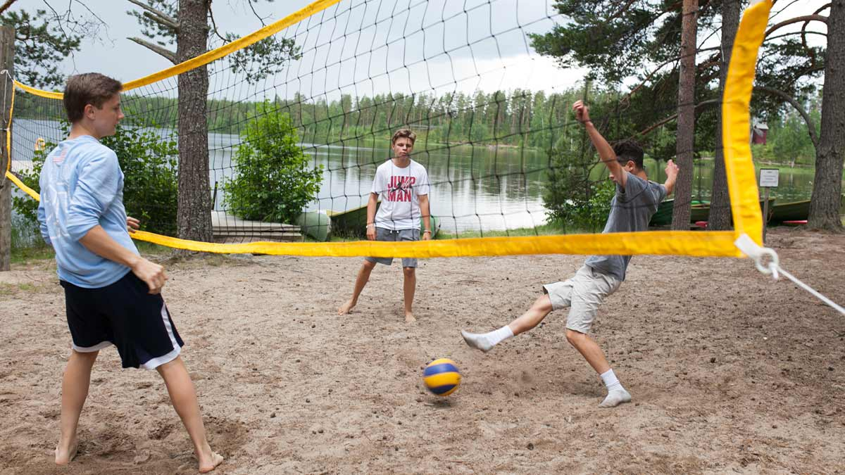 Kolme nuorta pelaamassa lentopalloa.