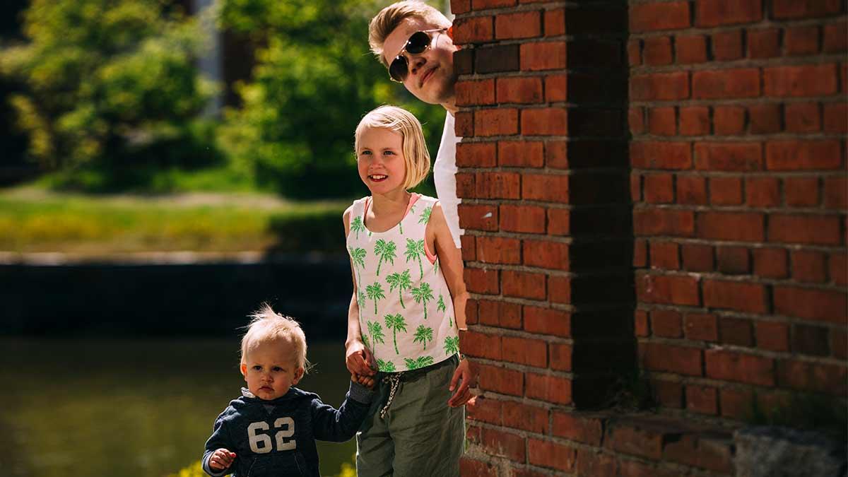 Taapero, nuori tyttö ja teini-ikäinen poika katsovat tiiliseinän takaa.