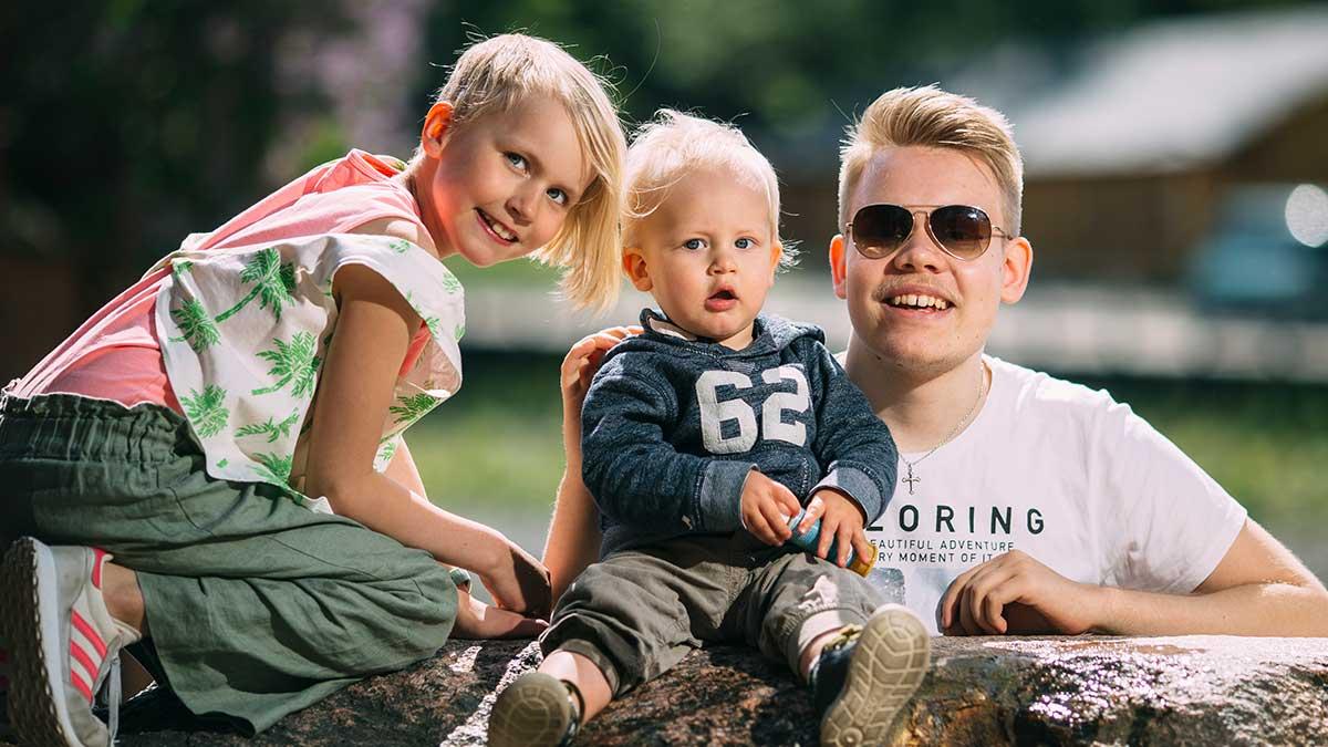 Lapsi, taapero ja teini istuvat kivellä.