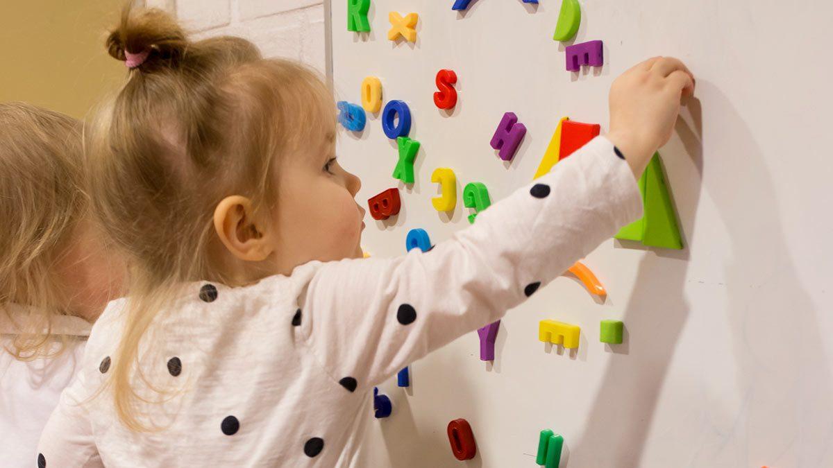Kaksi lasta leikkimässä magneettikirjaimilla.