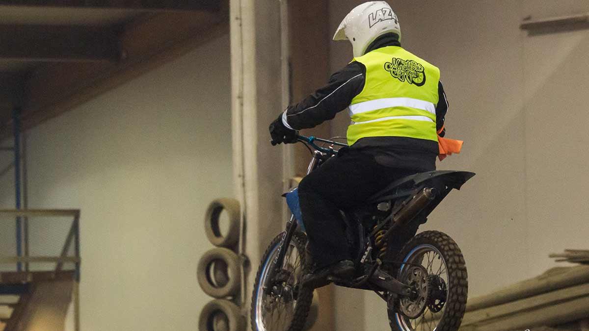 Mopoilija motocross-sisäradalla päällään Moottoripaja-huomioliivi.