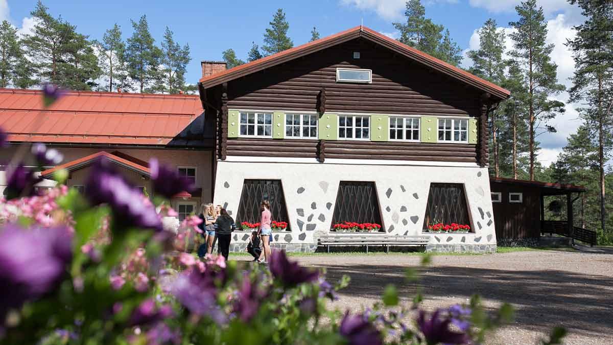 Partaharjun päärakennus. Kuvan etualalla kukkia.