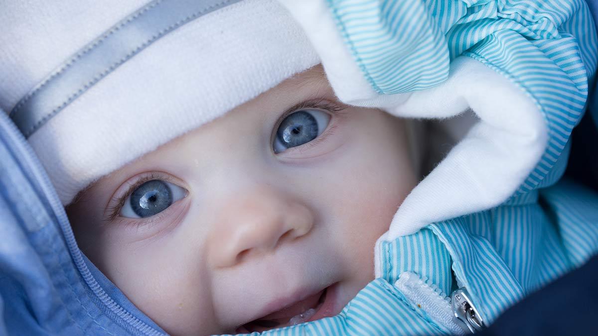 Vauva talvivaatteissa hymyilee.