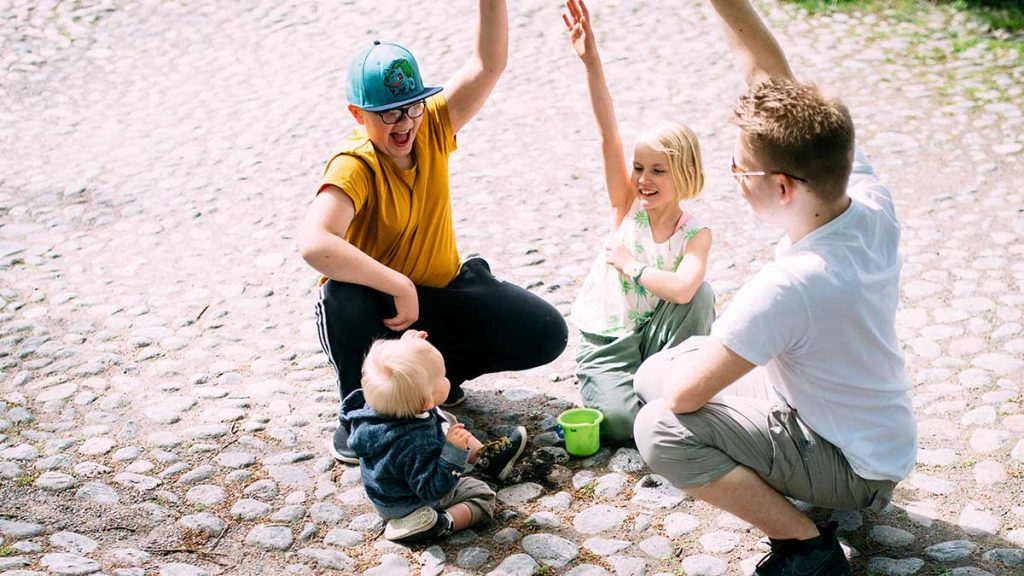 Taapero, nuori poika, nuori tyttö ja teini-ikäinen poika yhdessä nostamassa kädet ilmaan.