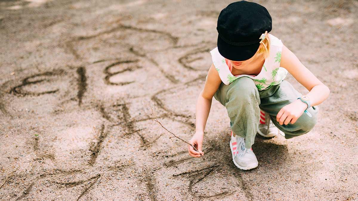 Nuori tyttö piirtämässä hiekkaan.