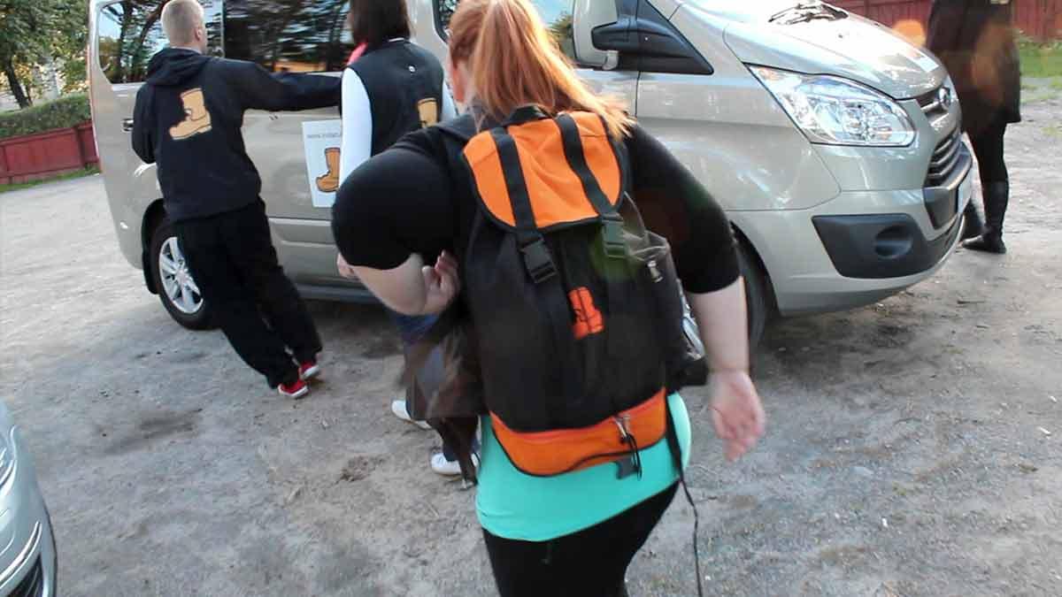 Päivitystäjä kävelämässä kohti pikkubussia selässään Saapas-reppu.