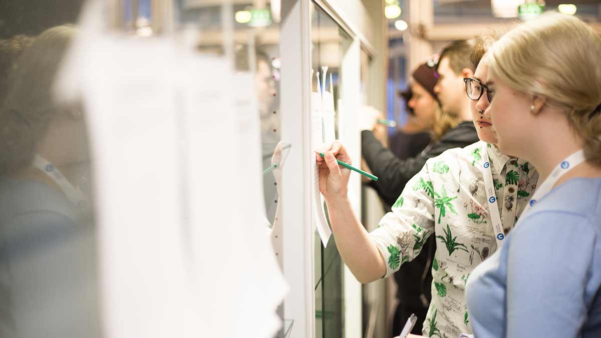 Nuoria kirjoittamassa seinälle kiinnitettyyn paperiin.