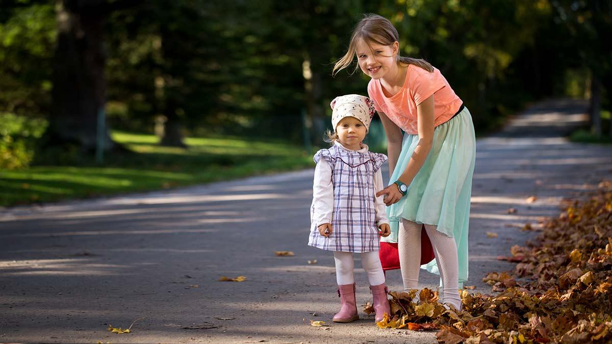 Lapsi pitää taaperon kädestä kiinni kävelytien reunalla. Molemmat katsovat kameraan, lapsi hymyilee.