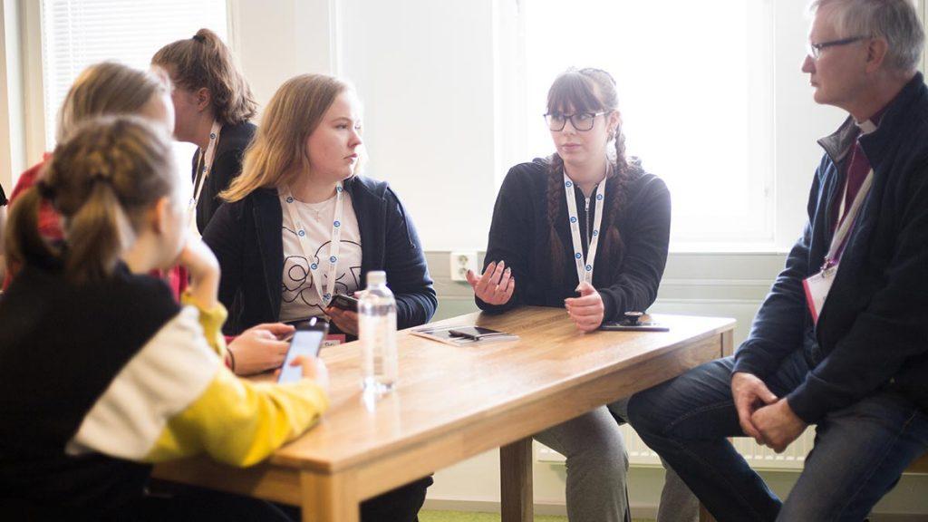 Joukko nuoria keskustelemassa piispa Seppo Häkkisen kanssa.