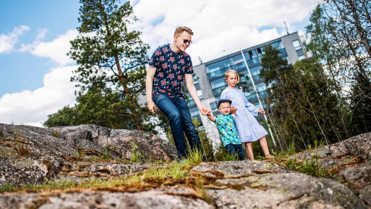 Lapsi, nuori ja taapero kävelevät käsikkäin.