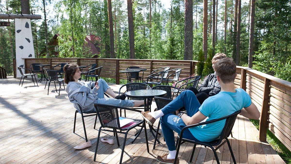 Kolme nuorta istuu ulkona terassilla pöydän ääressä