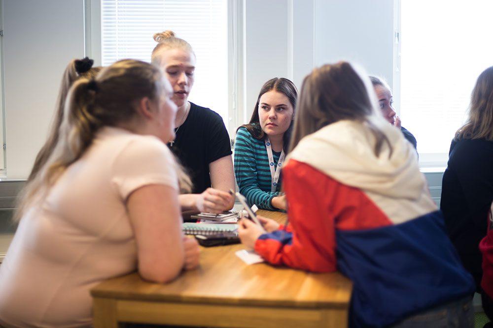 Nuoret istuvat pöydän ympärillä ja keskustelevat.