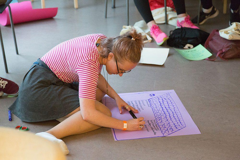 Nuori istuu lattialla ja kirjoittaa jotakin paperille.