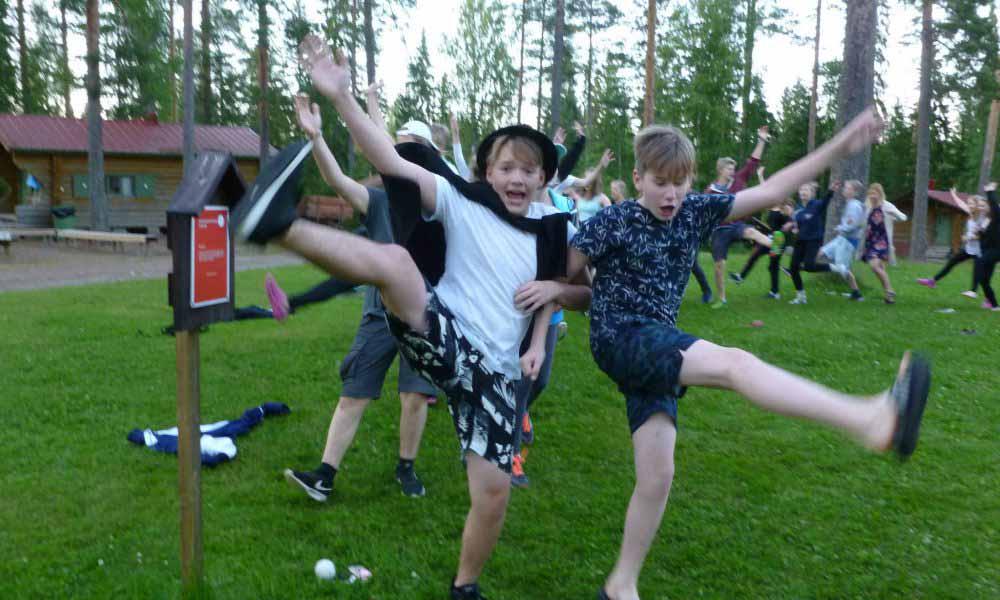 Nauravia nuoria käsikkäin leikkimässä yhteisleikkiä.