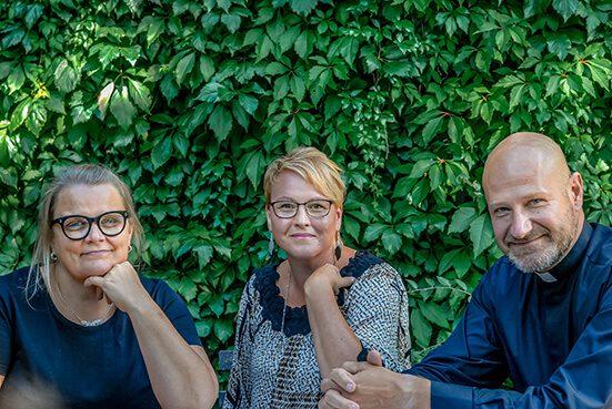 Kolme henkilöä seisovta vihreän pensasaidan edessä.