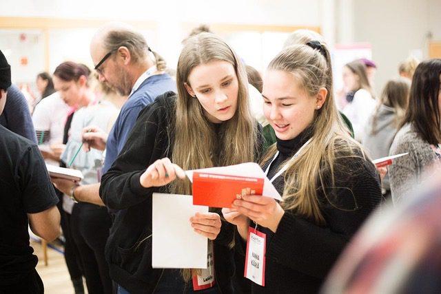 Kaksi nuorta tutkii Nuoren seurakunnan veisukirjaa