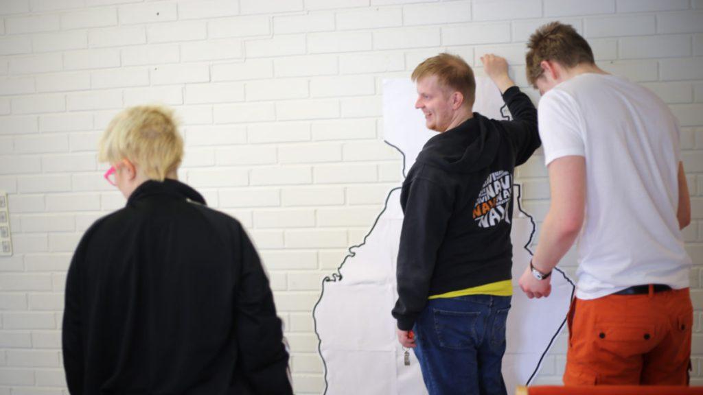 Nuori mies pitää Suomen karttaa vasten seinää ja hymyilee osallistujille