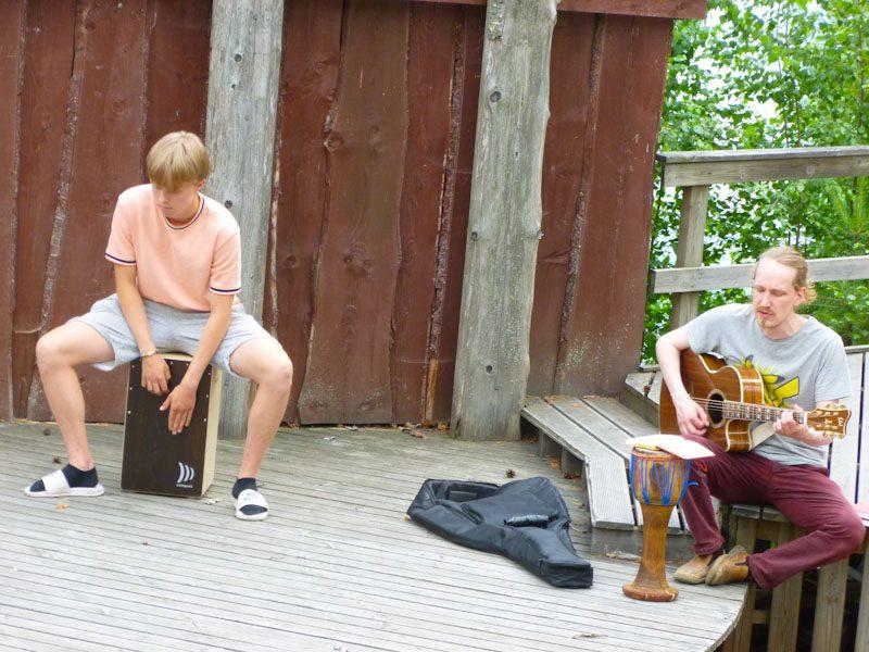 Kaksi miestä soittaa ulkoteatterilla. Nuorempi soittaa cajon-rumpua ja vanhempi istuen kitaraa.
