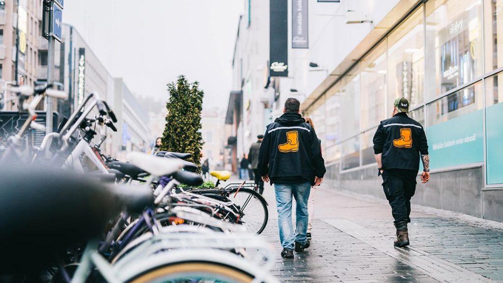 Kaksi Saappaan työntekijää kävelee kadulla poispäin