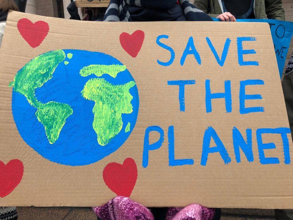 """Pahvikyltissä maan kuva ja vieressä teksti """"Save the planet""""."""
