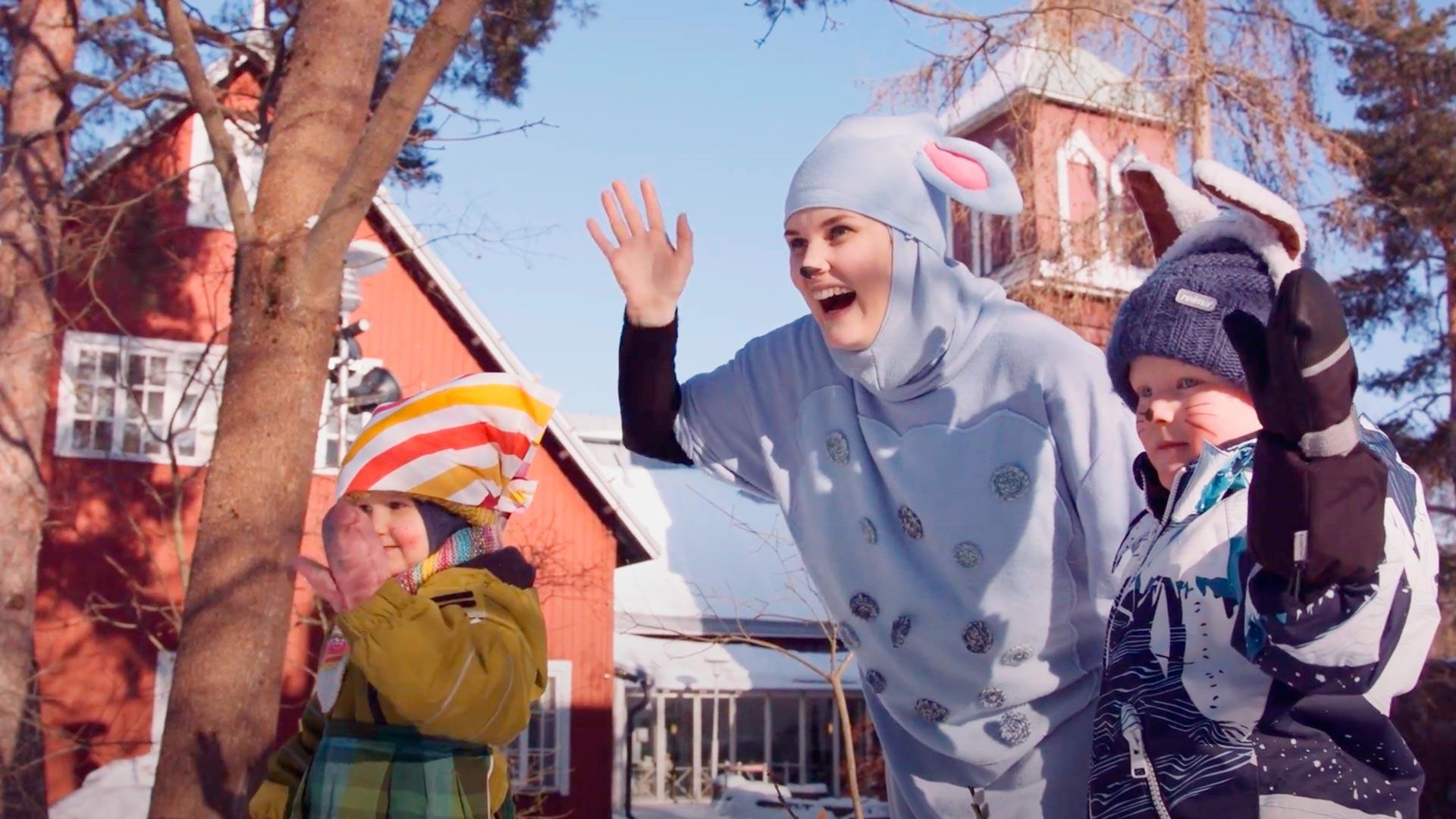 Kaksi lasta aurinkoisessa maisemassa heiluttaa ja heidän keskellään Lastenkirkon Päkä-lampaaksi pukeutunut näyttelijä