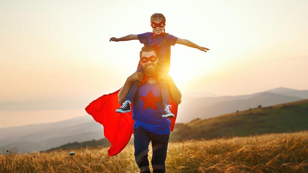 Kuvituskuva. Kummivanhempi kantaa olkapäillä kummilasta, molemmilla supersankariasut. Taustalla auringonlasku.