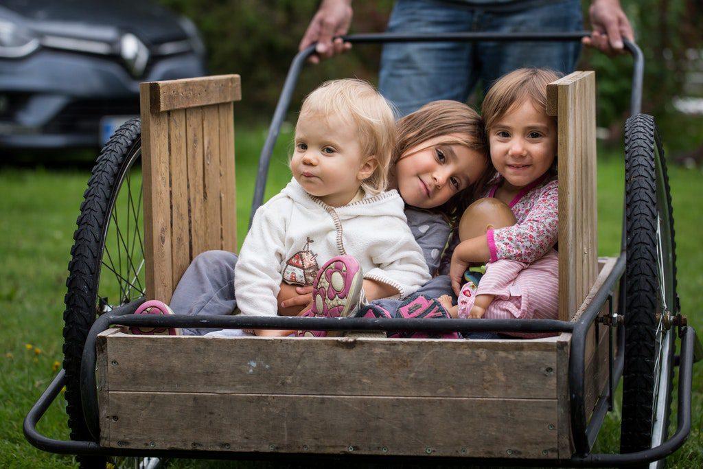 Kolme pientä lasta puukärryissä.