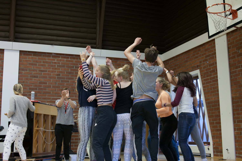 Nuoret tanssivat ja nauravat kädet ilmassa liikuntatilassa