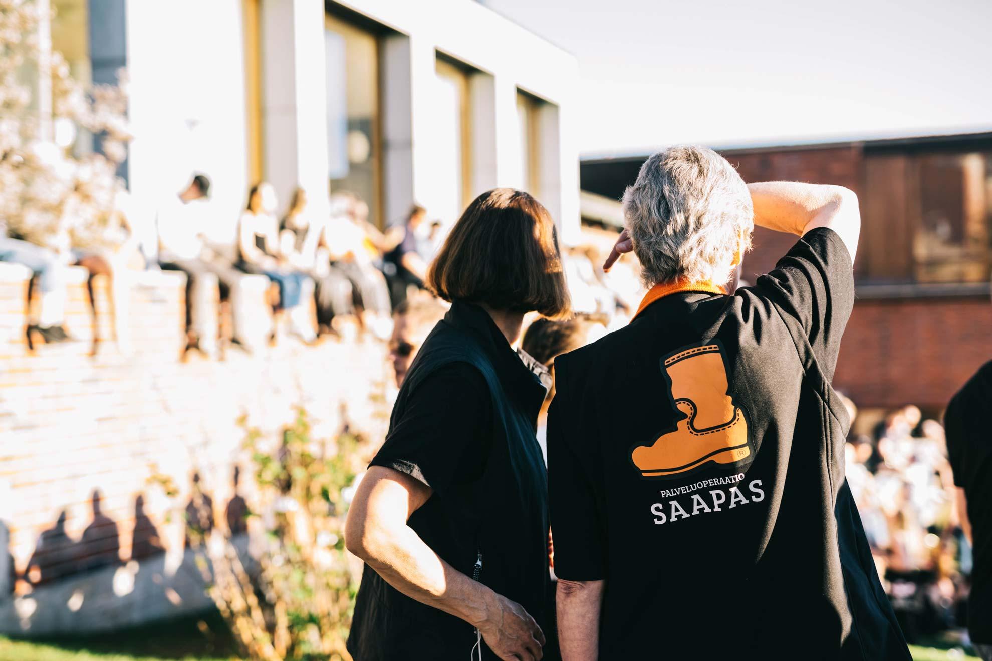 Kaksi Saappaan vapaaehtoistyöntekijää Saapas-liivit päällä katsovat horisonttiin. Edessä istuu nuoria muurilla.