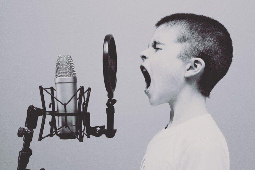 Poika huutaa mikrofoniin mustavalkoinen kuva