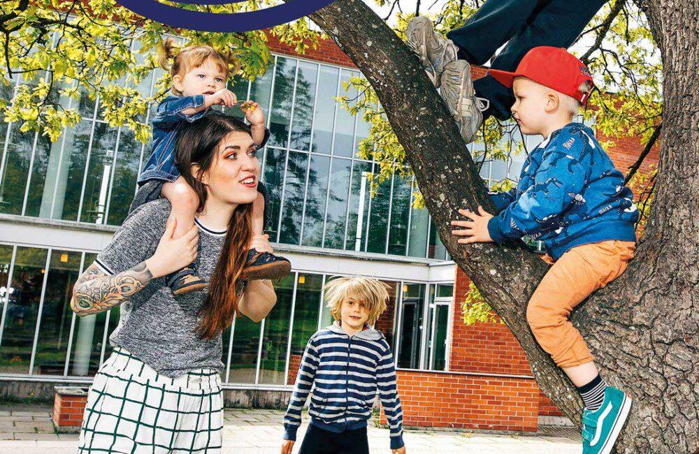 Kirkon pihalla joukko lapsia aikuisen kanssa. Vaaleatukkainen lapsi on kiivennyt puuhun ja katsoo aikuista, jonka olkapäällä on toinen pieni lapsi. Taustalla kouluikäinen poika hyppää. Tunnelma on iloinen ja kesäinen.