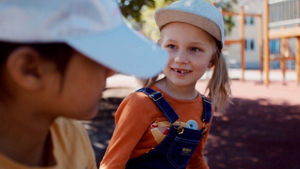 Hymyilevä lapsi katsoo toista lasta. Lapset ovat koulun pihalla ja tunnelma on kesäinen.