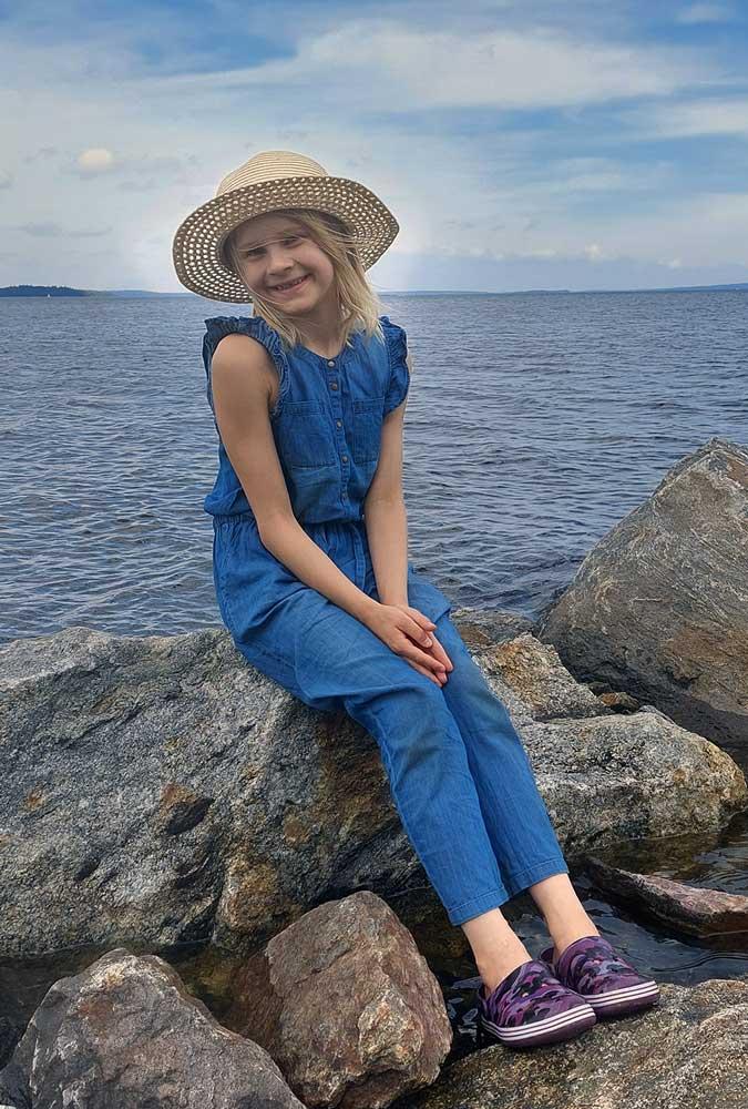 Lapsi istuu kivellä hattu päässä hymyillen