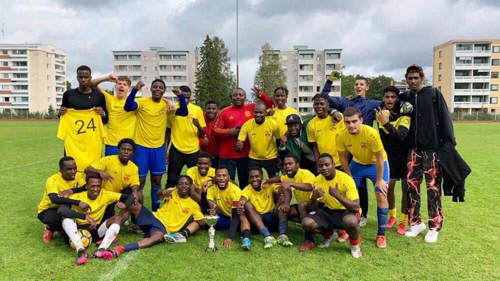 Pelaajat jalkapallokentällä ryhmässä. Osa näyttää voitonmerkkejä, tunnelma on iloinen.