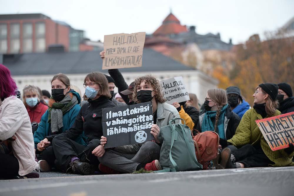 Ilmastoaktivisteja istumassa kadulla. Edessä istuvalla mielenosoittajalla kyltti: Ilmastokriisi vahingoittaa lähimmäistäsi.