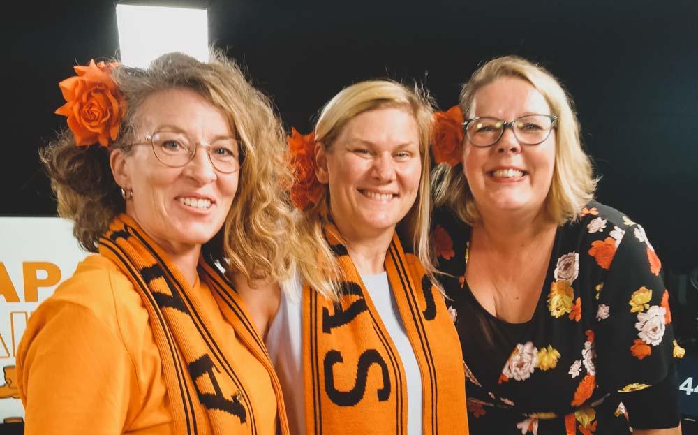 Kolme naista hymyilee. Kaulassa kahdella vasemmalla olevalla on oranssi huivi, jossa lukee Saapas. Kaikilla on hiuksissaan kukka.